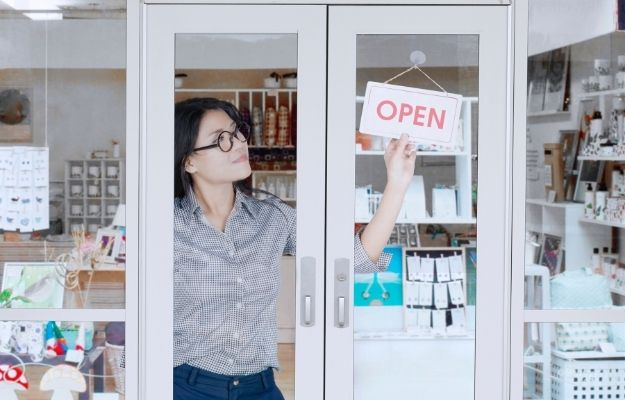 """Girl opening store - How to Mark My Business as Open   How to Mark My Business as Open?   Marking a Business as """"Temporarily Closed"""" and Search Rankings"""