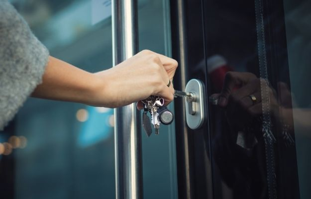 """Woman using key to lock door - Should You Mark Your Business Temporarily Closed   Should You Mark Your Business Temporarily Closed   Marking a Business as """"Temporarily Closed"""" and Search Rankings"""