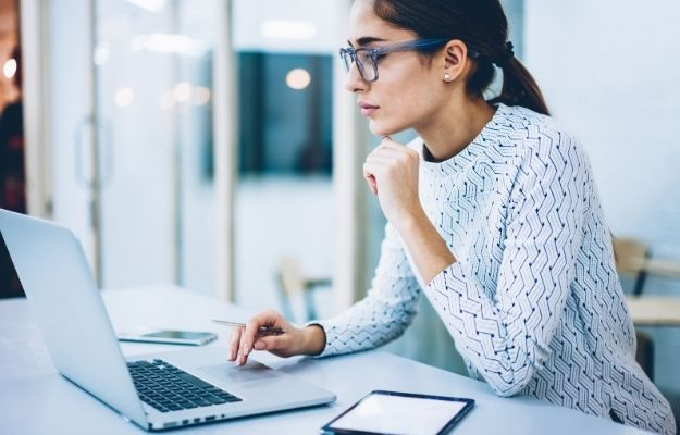 female manager checking updating on web page | How to Write Your Covid Update Business Description | How to Write Your Covid Update Business Description | The Importance of Updating Your Business Description During Covid-19