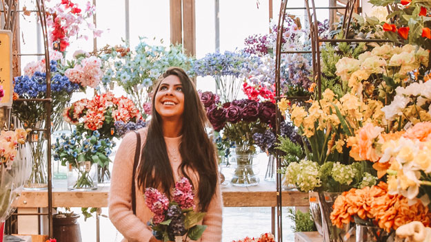 smiling_woman_in_flower_shop-sc | 5 Things Every Local Business Should Do To Boost Their Location Based Marketing | How Does Location-Based Marketing Work?