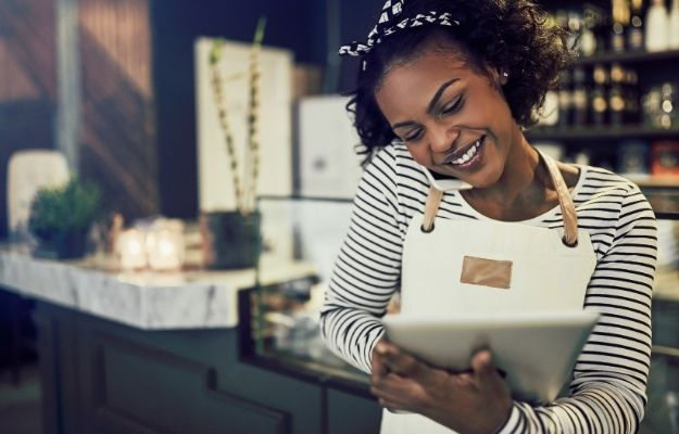 Black Girl in a shop while on her phone and holding a tablet - - Should I Add the Black-Owned Attribute | How to Add a Black-Owned Business Attribute to Your Google Maps