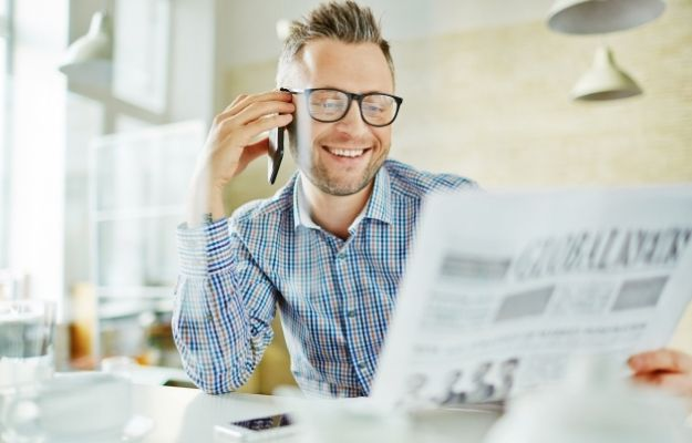 Guy talking on his phone while reading newspaper - Gain More Popularity Through Online Publication | Gain More Popularity Through Online Publication | 3 Franchise Marketing Ideas to Boost Local Business