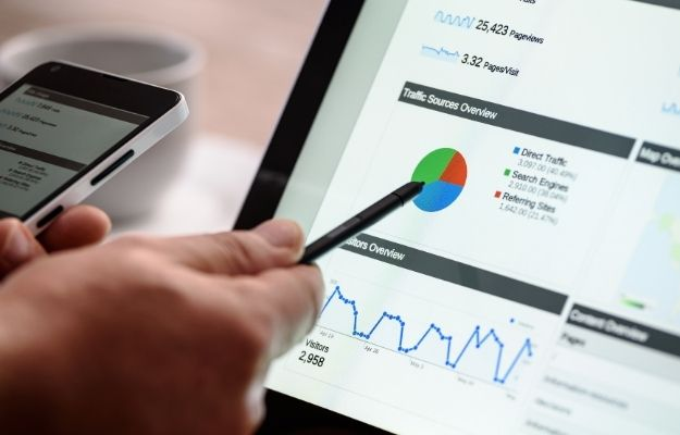 Person holding a phone while pointing at a computer screen showing charts and number with a pen - Utilize SEO for the Best Result | Utilize SEO for the Best Result | 3 Franchise Marketing Ideas to Boost Local Business