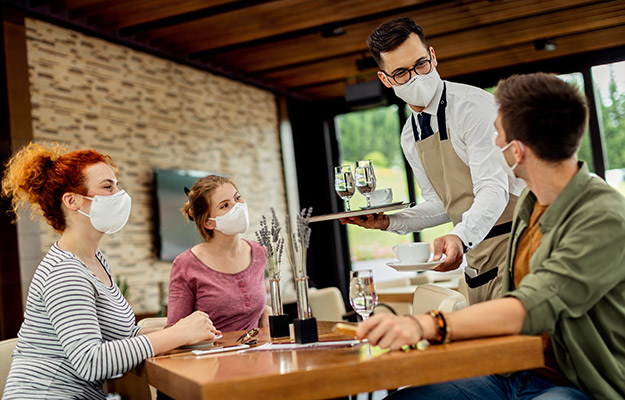 Group of people wearing mask in a coffee shop | How To Get More Foot Traffic To Your Business