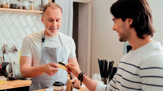 man-buying-coffee-with-card-at-coffee-shop-from-middle-aged-owner | Convert Searches to Sales with LOCL's Google Post Feature