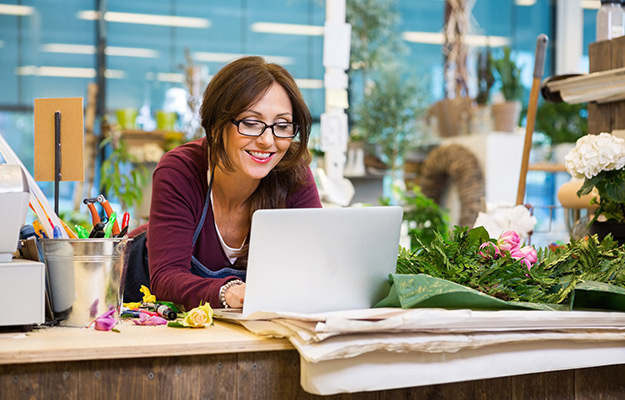 A flower store owner looking at the computer smiling | How Photos Can Increase Your Google My Business Listing Performance