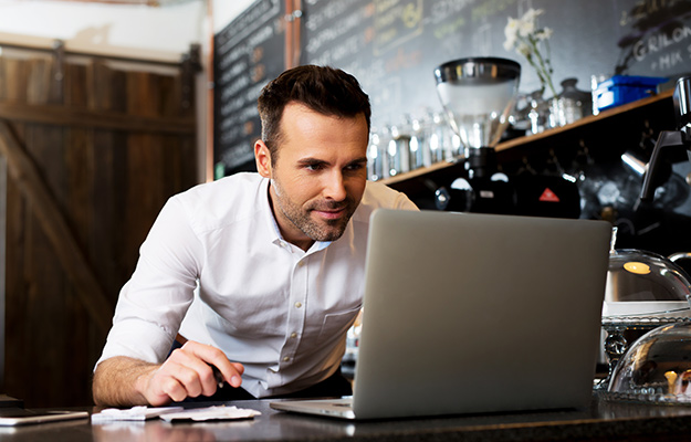 Smiling man looking at laptop | Improve Your Multi-Location Business Marketing With Locl